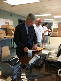 Ron Rose watches as the Senator prepares a package for shipping.  Steve Hultquist appears in the background.