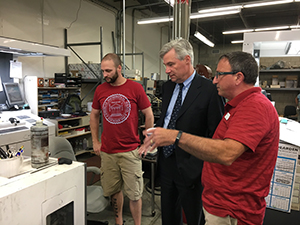 The Senator is shown the machines by Don Proulx (right) and Jonathan Oulette (left).