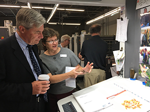 Catherine Roberts showing Senator Whitehouse the 2018 Calendar of Mathematical Imagery hot off the press.