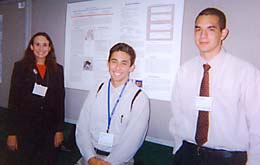 Tiffany Hegg, Brandon Brown and Adgar Cabral in front of their poster on work done at the MTBI